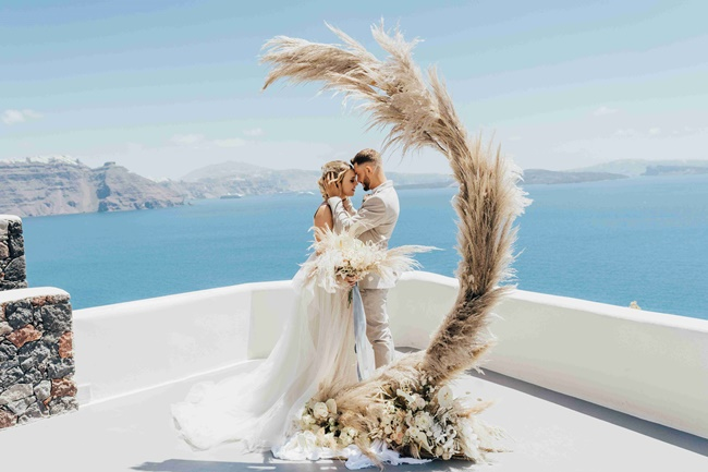 Modern and minimal ceremony arch with pampas grass in Santorini Greece
